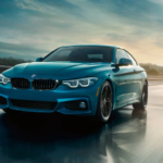 Teal BMW 4 Series on city highway