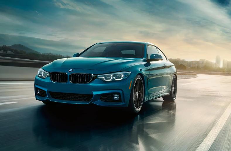 Teal BMW 4 Series on city highway
