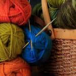 Red, Blue, and Green yarn balls with knitting needles near a wicker basket.