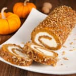 Sliced pumpkin roll on a plate.
