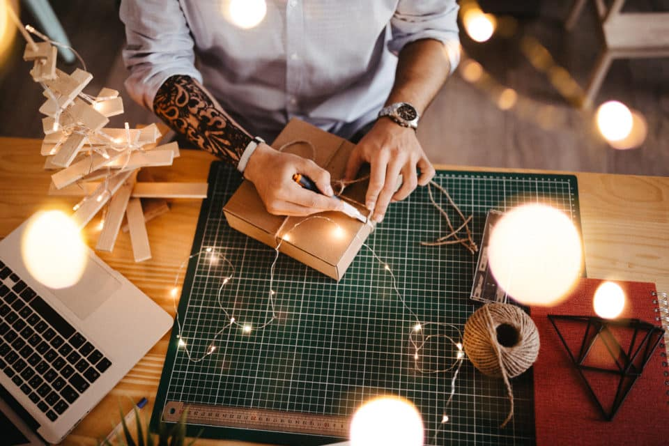 Hipster man with tattoo on his hand sitting at work and wrapping gift box.