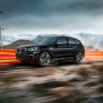 BMW X3 SUV on a desert road with blurred lines of light in the background