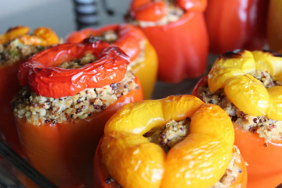 Four bell peppers stuffed with quinoa and roasted.