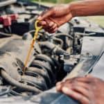 hands pulling oil dipstick under hood of car