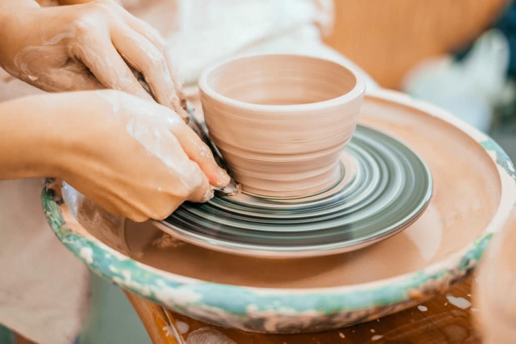 Woman working on a pottery wheel to make a mug