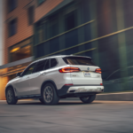 A white 2021 BMW X5 SUV driving in the city