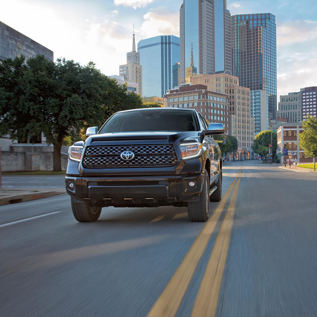 The 2020 Toyota Tundra model features at Boch Toyota in Norwood | Black MY20 Tundra driving down empty city street