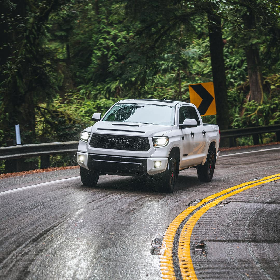 The 2020 Toyota Tundra model features at Boch Toyota in Norwood | White MY20 Tundra making a turn on an empty wet road