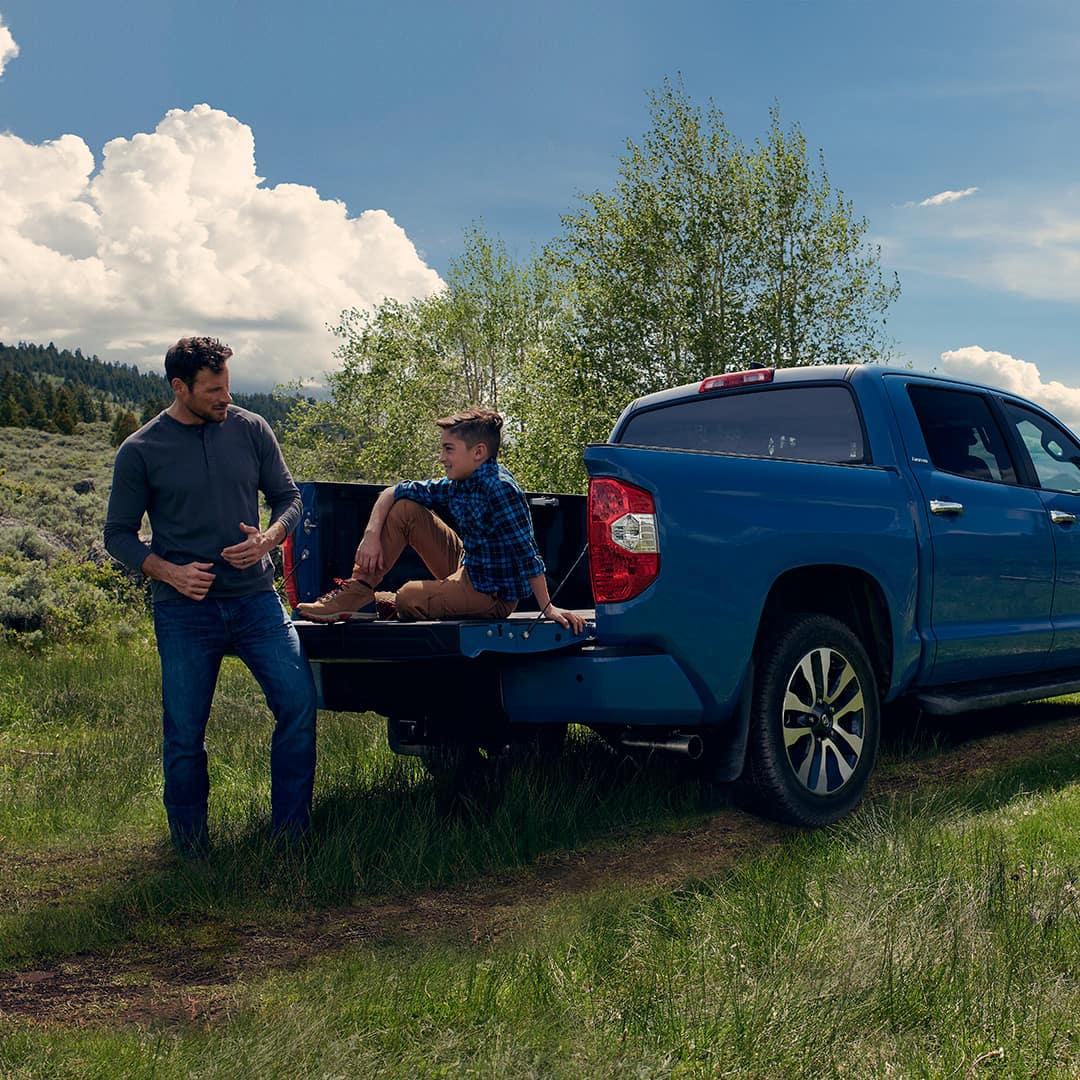 The 2020 Toyota Tundra model features at Boch Toyota in Norwood   Father with his son siiting in the flatbed of the Blue MY20 Tundra