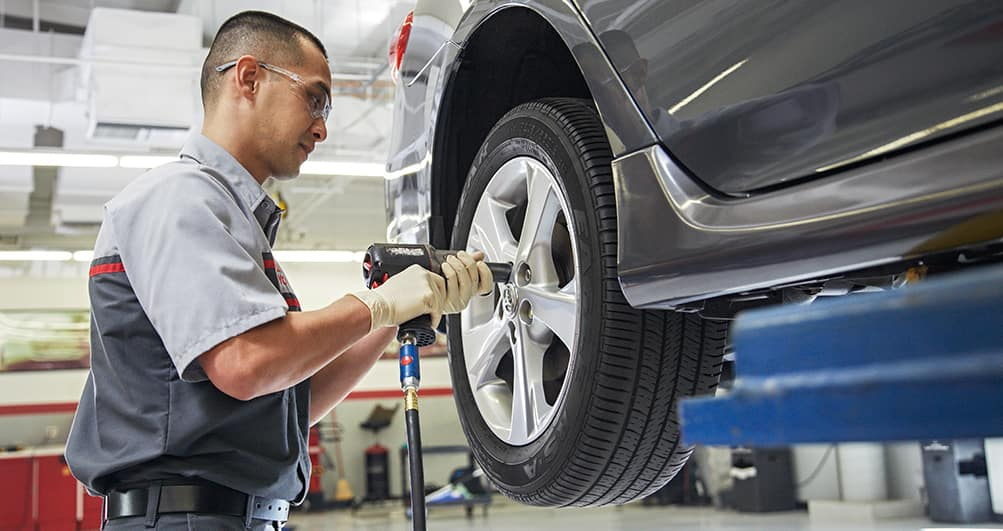 ToyotaCare in Norwood at Boch Toyota | Technician changing tire