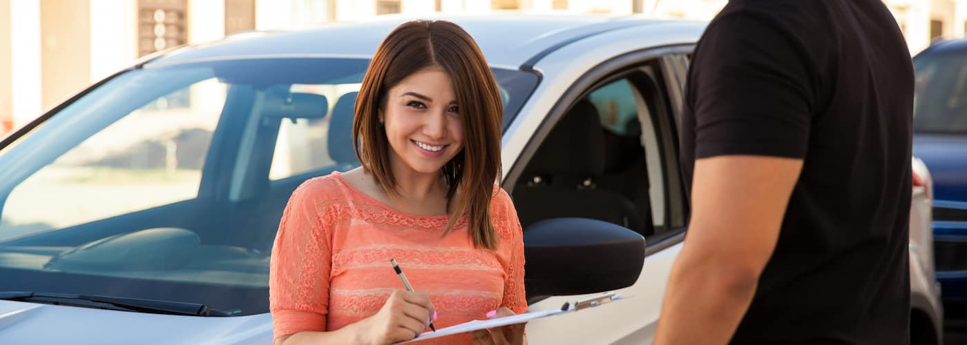woman signing a financing plan in front of blurred car