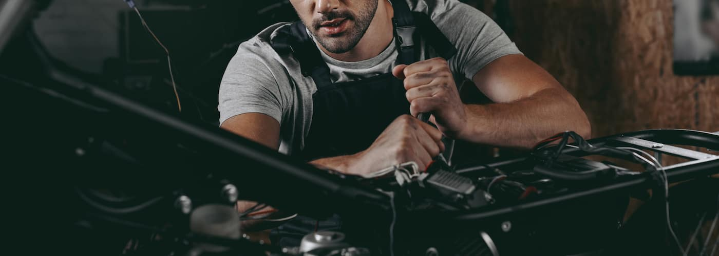 motorcycle mechanic working on motorcycle