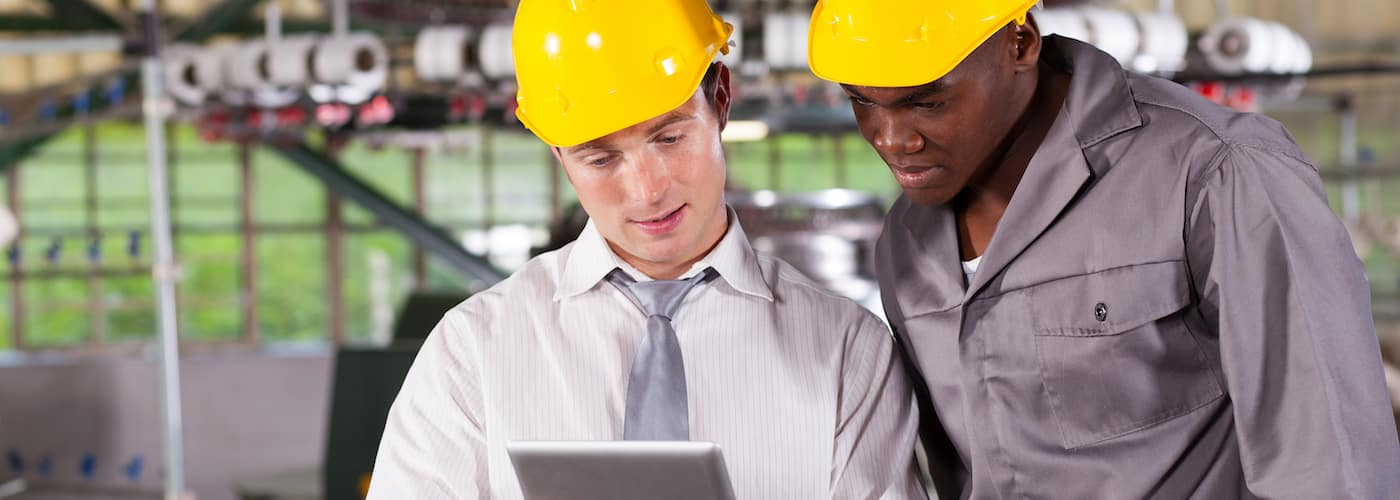 two men in hardhats in car manufacturing plant
