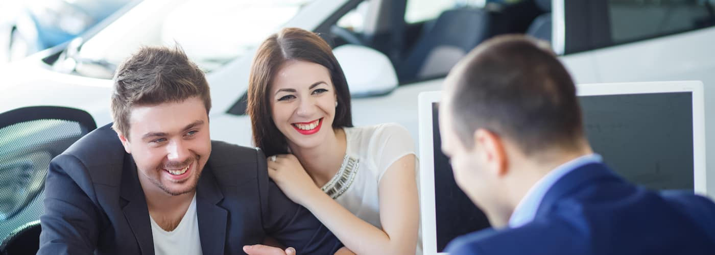 car salesman reviewing car details with happy smiling couple and blurred out car in background
