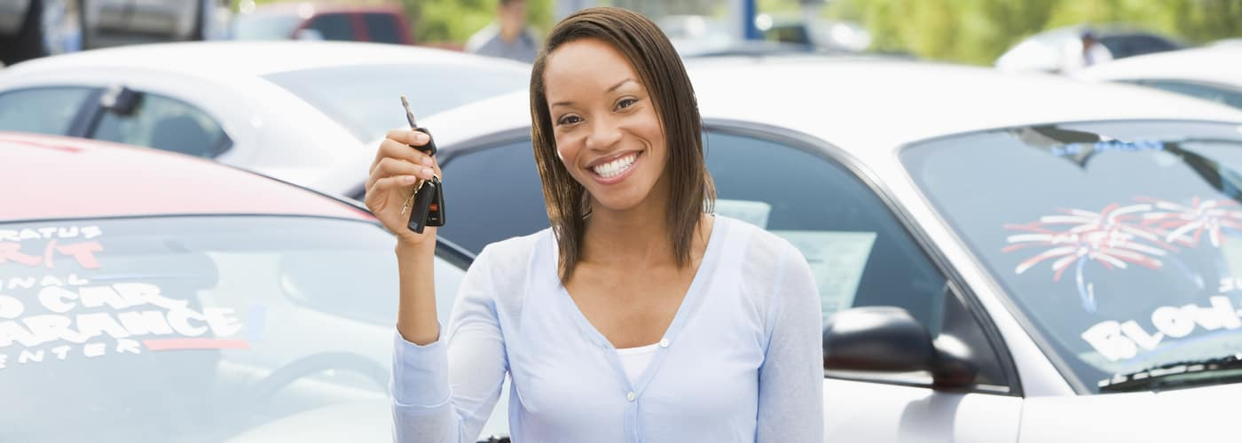 woman holding up keys and smiling while sitting on car closeup