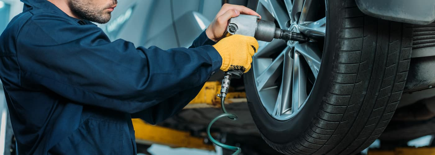 mechanic performing maintenance on car tire close up
