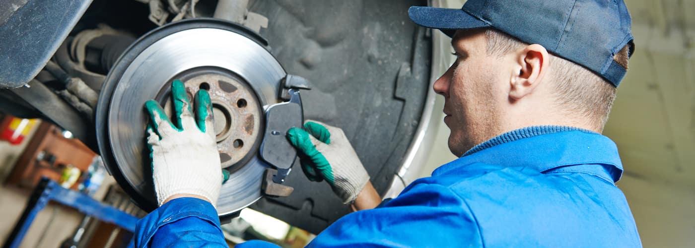 close up of mechanic repairing suspensions and brakes