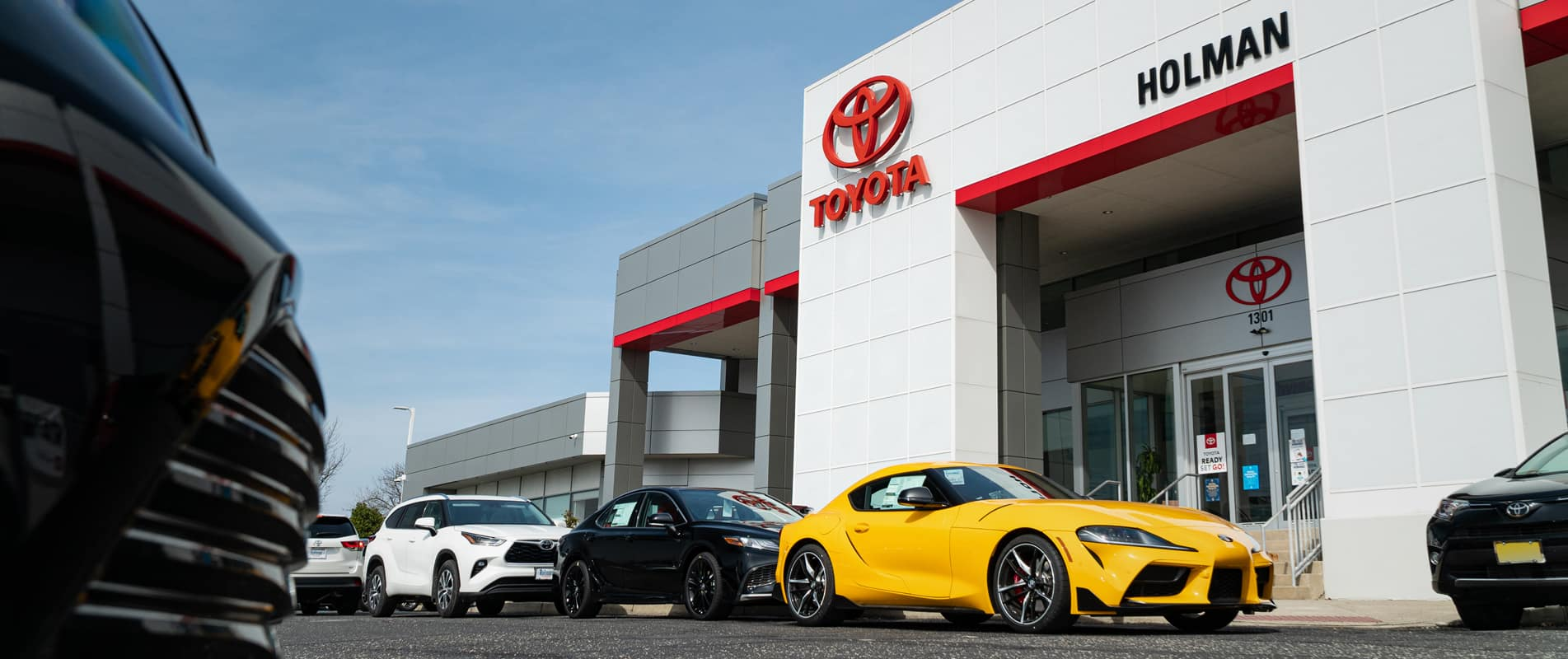 Dealership front with lineup of cars