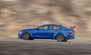 Blue 2019 Jaguar XE SV Project 8 riding fast on mountain side