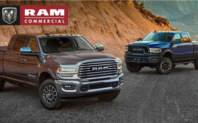 Two Ram trucks parked on a mountain road