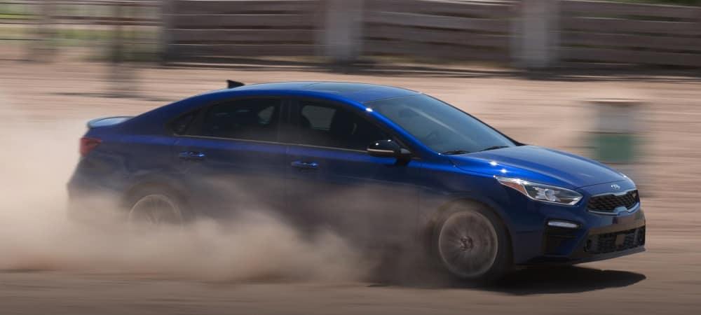 blue-kia-forte-driving-through-dry-dirt
