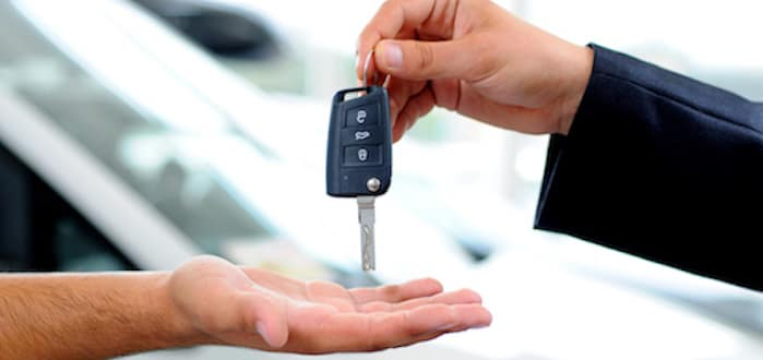 Salesman handing car keys to customer