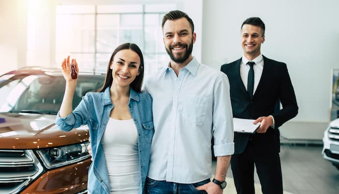 Smiling couple holding car keys in showroom with car salesman in background
