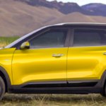 Yellow Kia Seltos parked with mountains in background