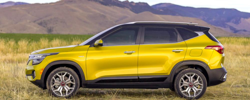 Yellow Kia Seltos parked with mountains in background