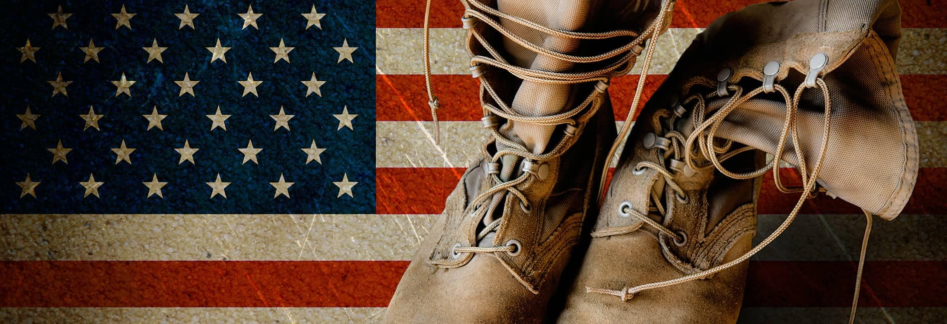 Worn leather boots sitting atop a faded American flag