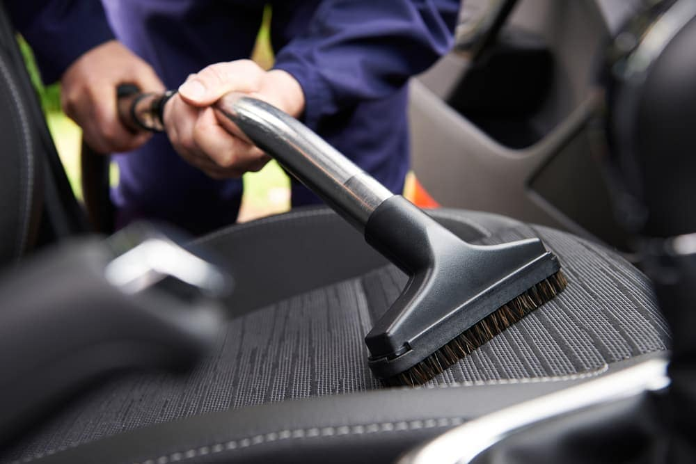 Worker vacuuming car