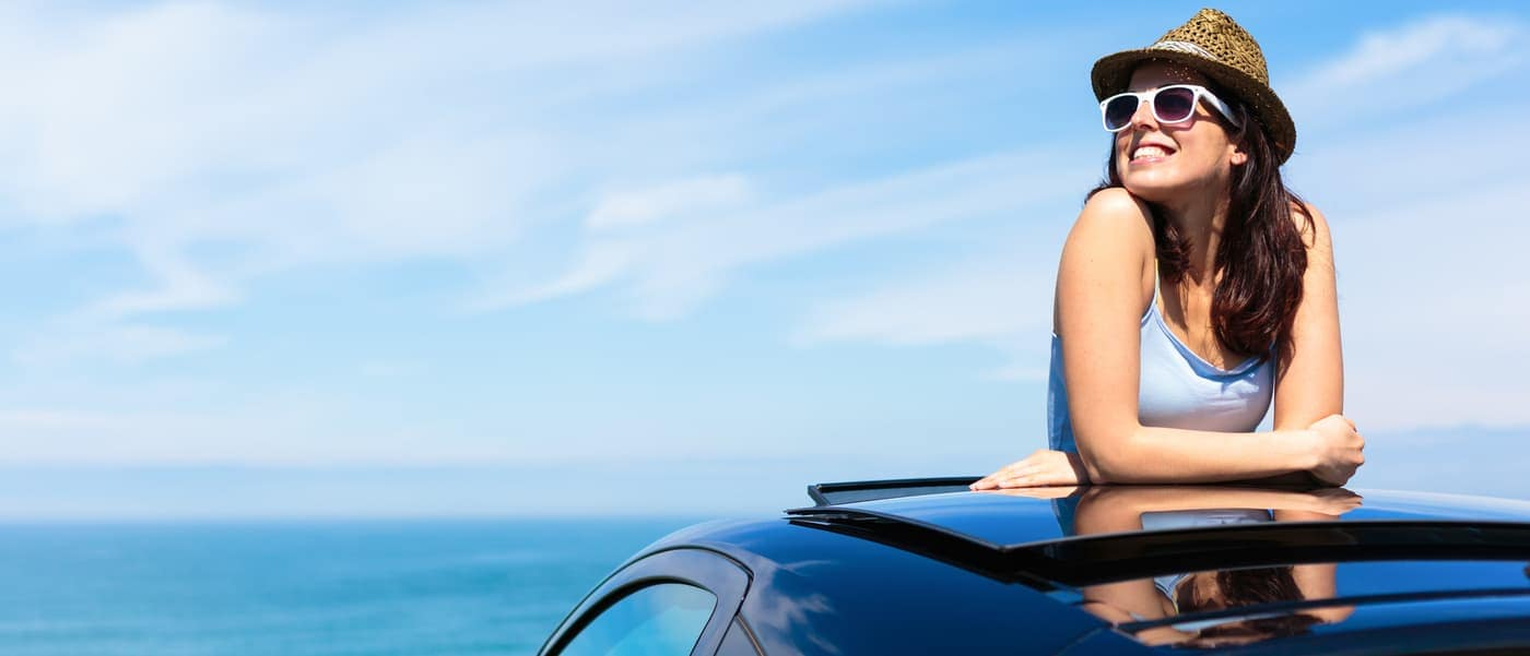 woman poking through sunroof of car
