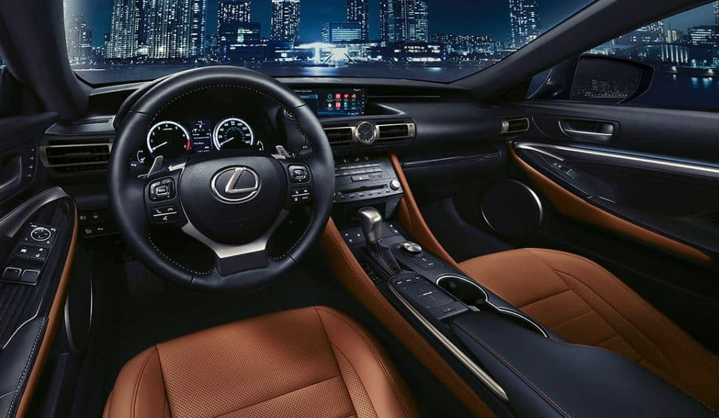 Lexus RC 2019 brown leather interior lit up agains city skyline showing technology dashboard features including Alexa interface