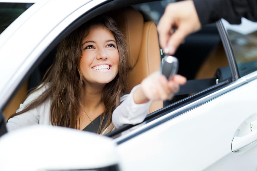 Smiling young woman in driver seat of her new car happy with her preowned vehicle purchase being handed the car keys