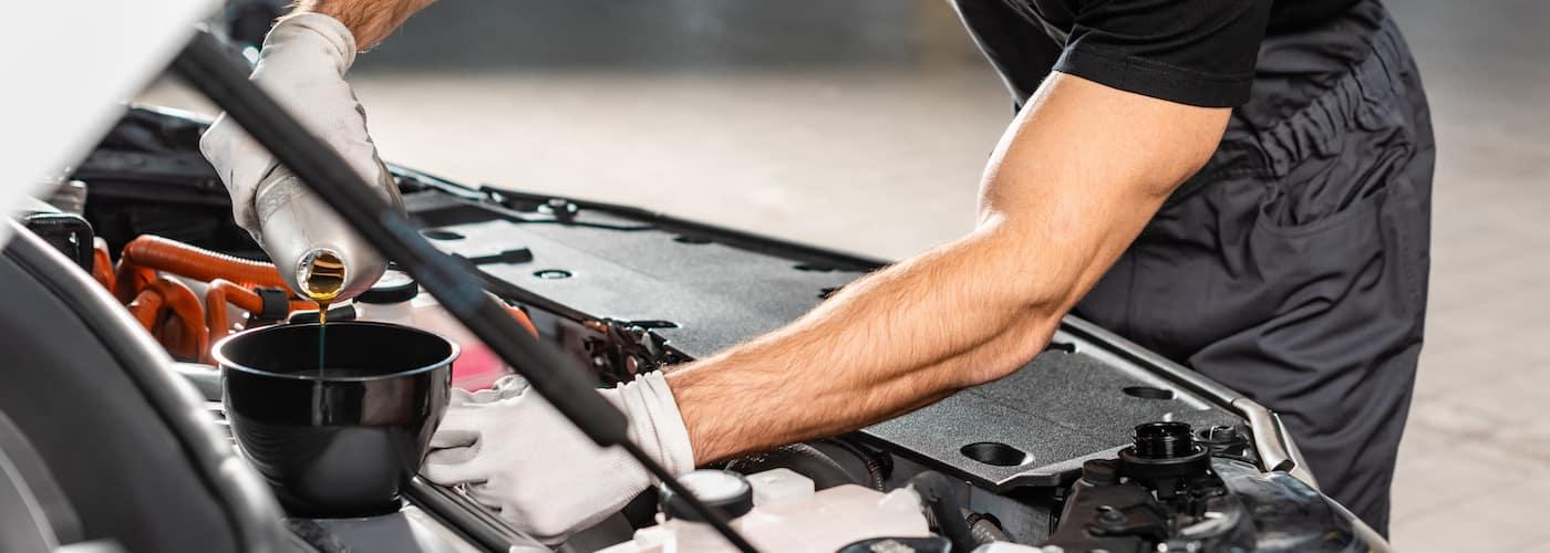 mechanic adding new oil to car