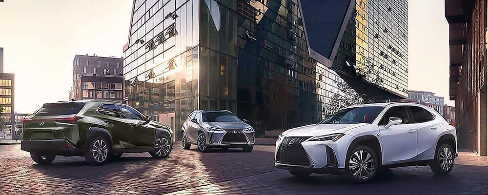Black, silver and gray Lexus SUVs in city at sunrise