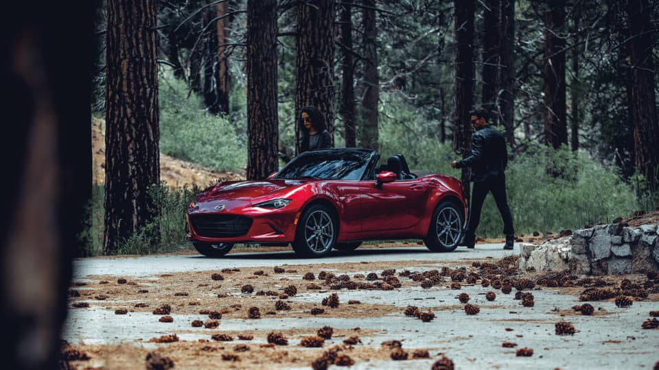 A red 2020 Mazda Miata in a forest; a couple is about to enter the vehicle.