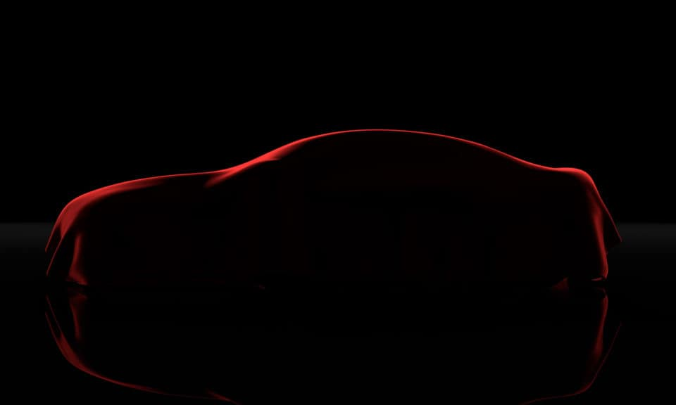 Car covered with a red cloth isolated on a black background