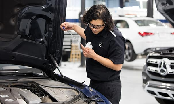 mercedes-benz trained technician checking a dipstick of a vehicle
