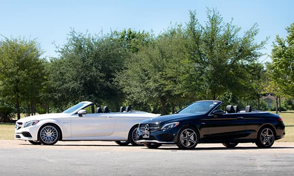 two mercedes-benz cabriolets with the tops down in the sunshine of a nature setting