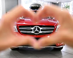 person holding heart hands with MB logo in background