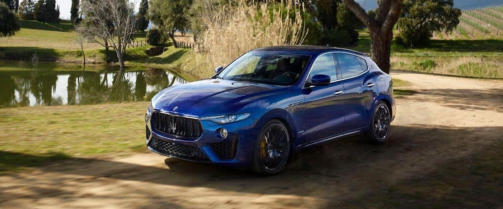 A 2020 Maserati Levante driving on a dirt road in the country