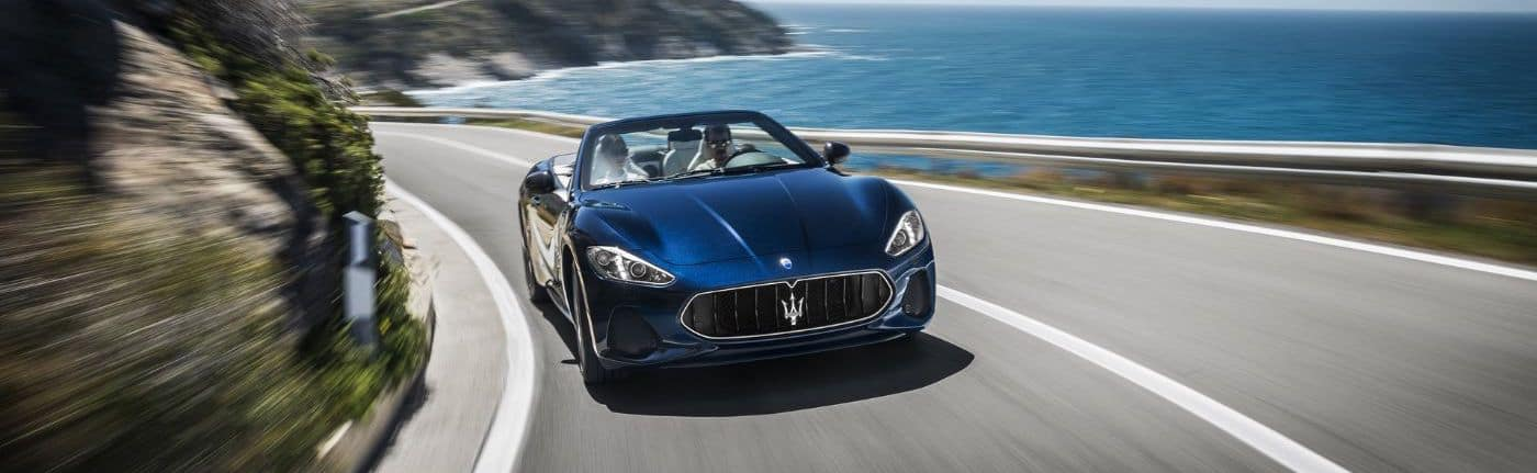 A 2020 Maserati GT convertible driving on a highway overlooking the ocean