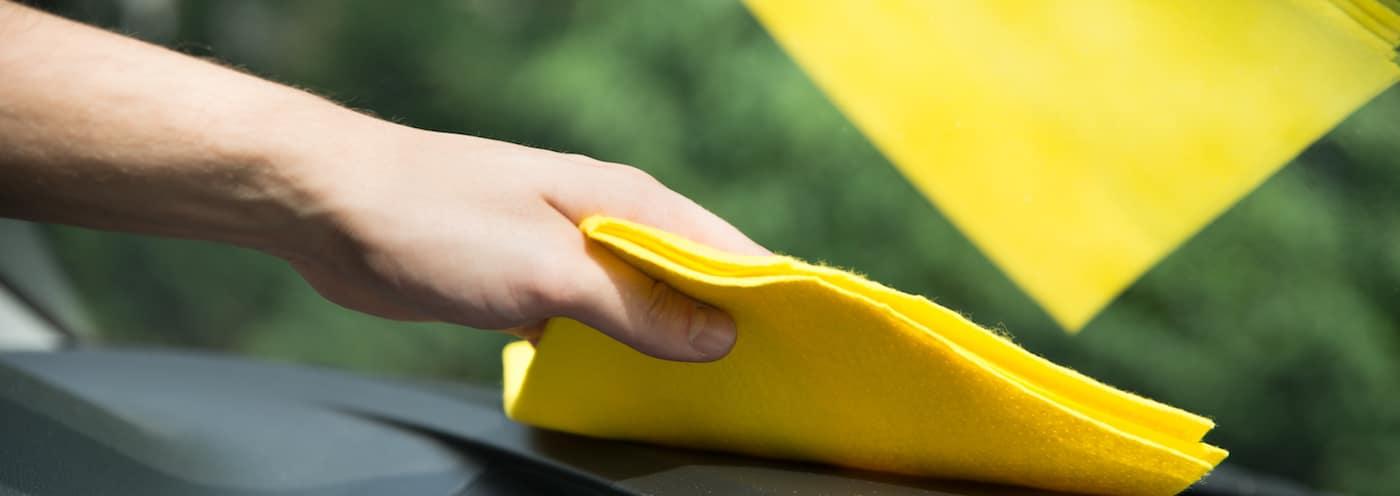 Mans hand sterilizing a car with a rag