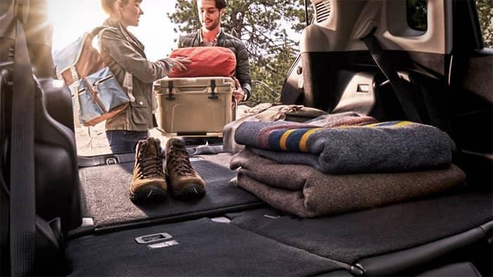 Couple loading supplies into cargo area of Jeep Compass