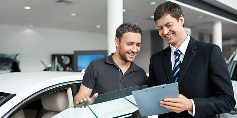 Man signing papers with sales person