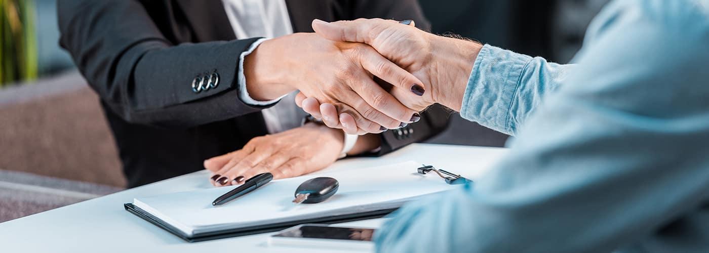 Woman salesperson shaking mans hand
