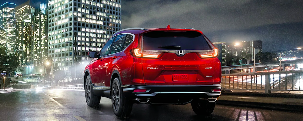 Rear view of a 2020 Honda CR-V driving on a city street at night
