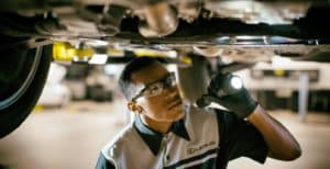 a gloved Lexus Service technician looking a undercarriage of car with flashlight