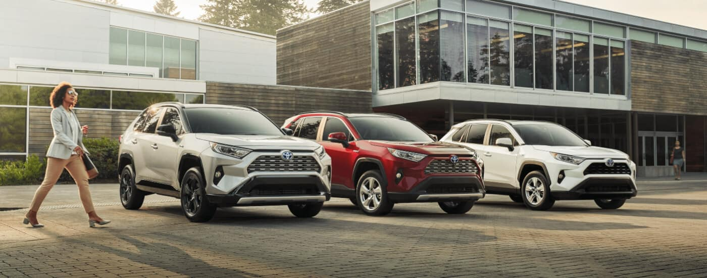 woman walking beside 3 2020 Toyota Rav4 models